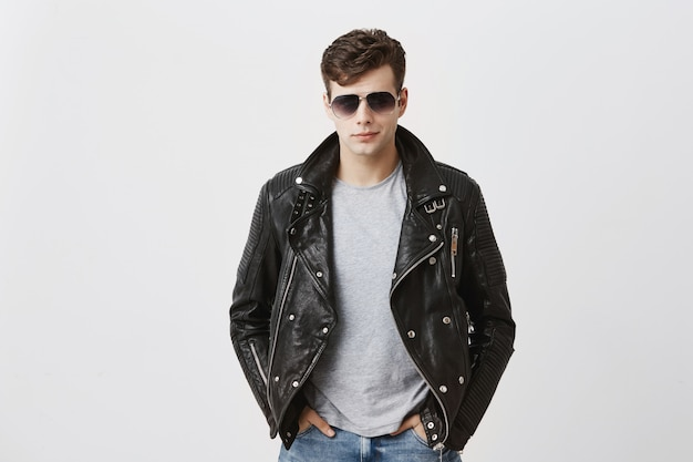 Confident serious handsome man wears black leather jacket over gray t-shirt and stylish eyewear, looks directly into camera, isolated . people and style concept