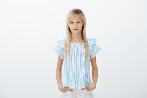 Fiduciosa ragazza bionda dall'aspetto serio in abiti blu, tenendo le mani in tasca e sorridendo ampiamente durante l'audizione dei bambini, essendo sicura di sé e rilassata sul muro grigio
