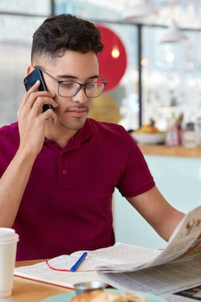 自信を持って真面目な男性経営者は、日刊紙で金融ニュースを読み、電話で会話し、コーヒーショップのテーブルで新鮮な飲み物を飲みながらモデルを作り、メモ帳でメモを取ります。縦ショット