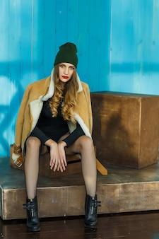 Уверенная в себе сексуальная девушка в коричневой дубленке и шляпе с чулками сидит на подиуме и смотрит в камеру на синюю деревянную стену.