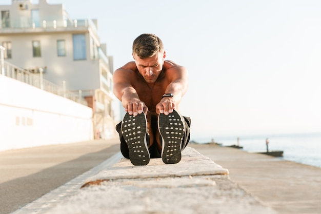 Confident shirtless sportsman doing stretching exercises