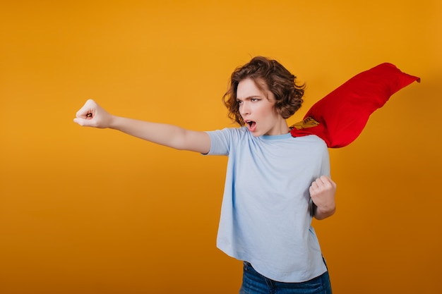 Confident short-haired girl posing in red superhero cloak