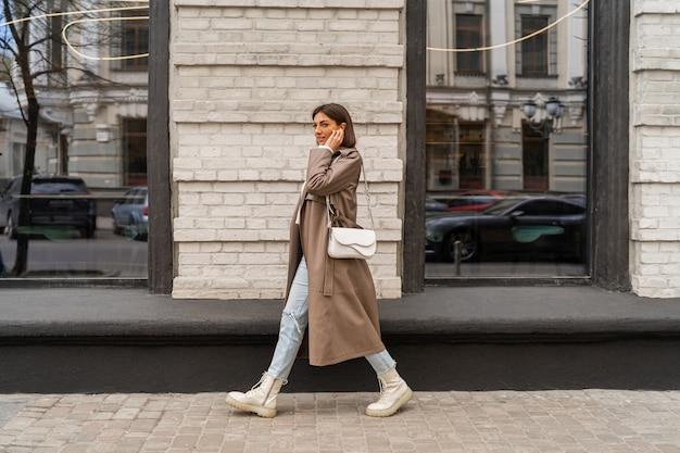 캐주얼 베이지색 코트와 흰색 질감의 가죽 숄더백을 입은 자신감 있는 짧은 머리 여성, 유럽 도시의 거리를 걷고 있습니다.