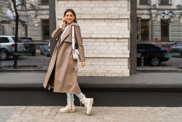 Confident short haired woman wearing casual beige color coat and white textured leather shoulder bag, walking in street of european city