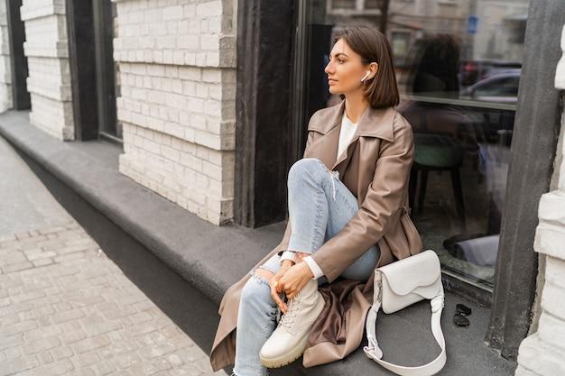 트렌디한 베이지색 코트와 흰색 질감의 가죽 숄더백을 입은 자신감 있는 짧은 머리 여성, 유럽 도시의 거리를 걷고 있습니다.