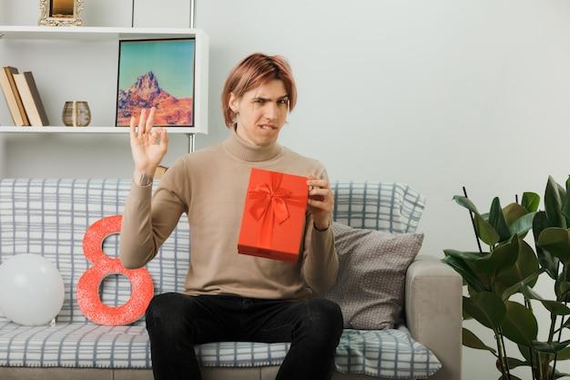 Красивый парень уверенно показывает хороший жест в счастливый женский день, держа в руках подарок, сидя на диване в гостиной