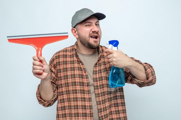 Уверенный славянский уборщик моргает и держит ракель со спреем для чистки