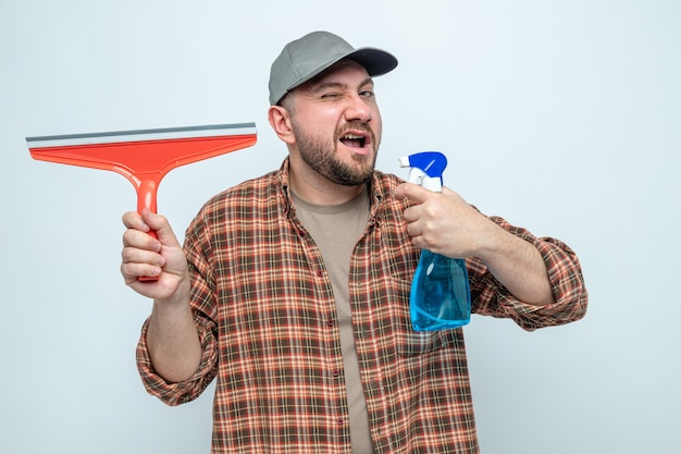 Confident slavic cleaner man blinking his eye and holding squeegee with spray cleaner
