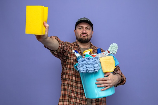 Confident slavic cleaner man holding cleaning equipment and sponge