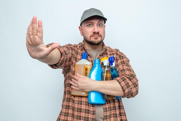 Fiducioso pulitore slavo uomo che tiene in mano spray e liquidi per la pulizia che gestualizzano il segnale di stop