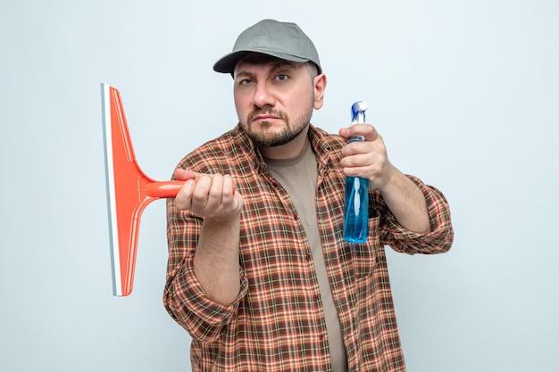 Уверенный славянский уборщик, держащий ракель и спрей-очиститель