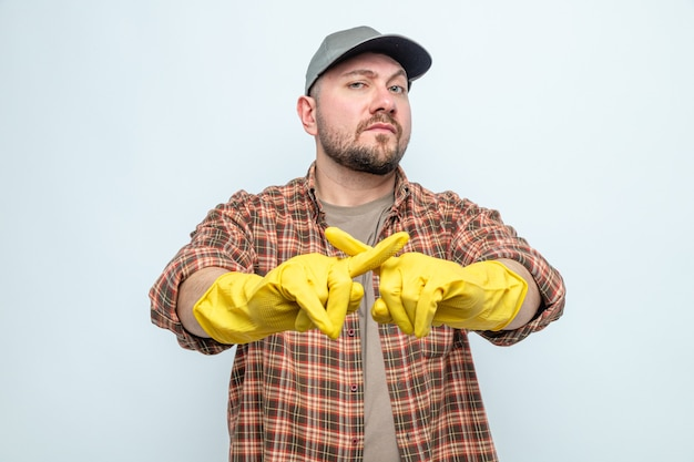 Confident slavic cleaner man with rubber gloves crossing her fingers gesturing no sign