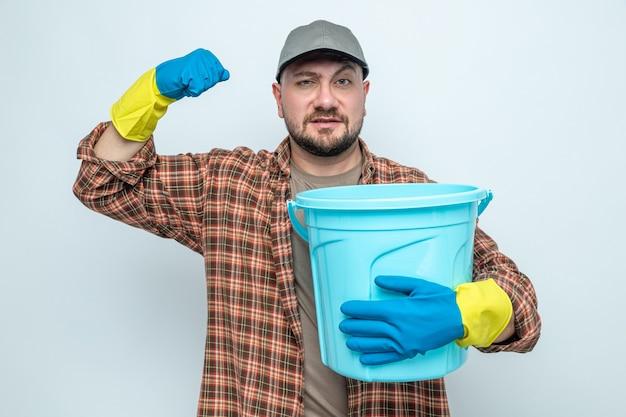 Fiducioso uomo delle pulizie slavo con guanti di gomma che tiene il secchio e alza il pugno