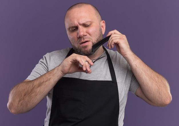 Уверенный славянский парикмахер средних лет в униформе стригет бороду ножницами, изолированными на фиолетовой стене
