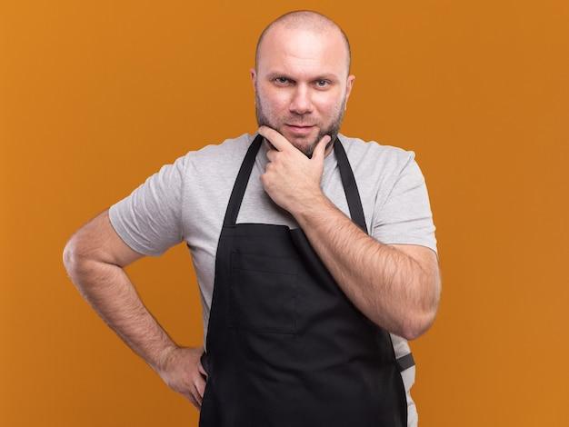 Il barbiere maschio di mezza età slavo sicuro in uniforme ha afferrato il mento che mette la mano sull'anca isolata sulla parete arancione
