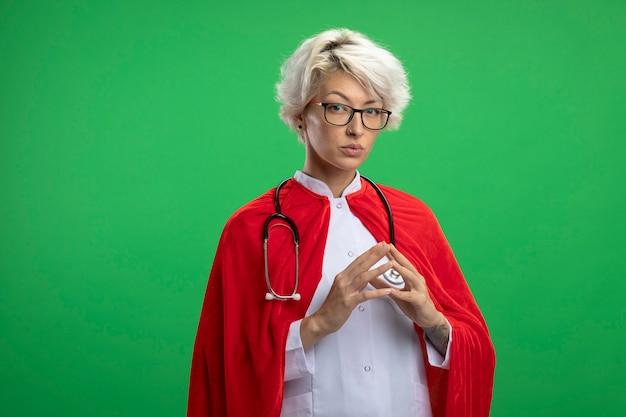La donna sicura del supereroe slavo in uniforme del medico con il mantello rosso e lo stetoscopio in vetri ottici tiene le mani insieme isolate sulla parete verde con lo spazio della copia
