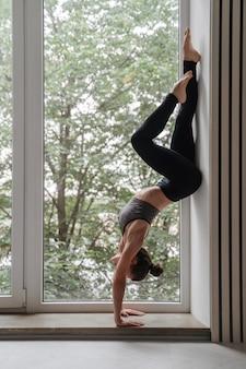 Confident slim brunette woman in sportswear doing handstand against wall near big window