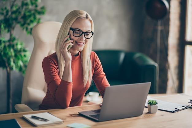 자신감이 똑똑한 최고 보스 여자 앉아 테이블 의자는 컴퓨터에서 고객 유형과 대화를 나누고 사무실 로프트 워크 스테이션에서 빨간 터틀넥을 착용하십시오.
