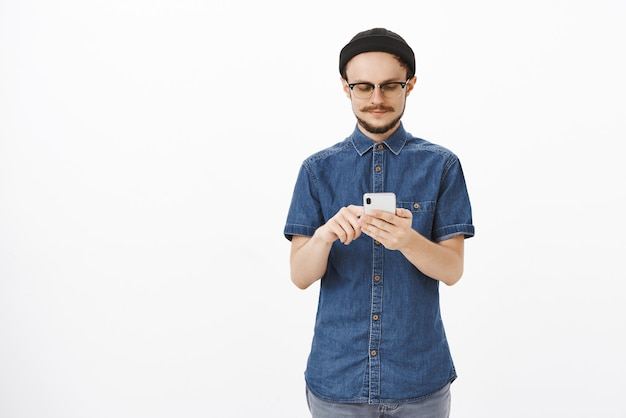 Confident smart and creative male studio manager in beanie and glasses with beard typing message in smartphone or searching information in internet gazing at gadget screen relaxed over gray wall