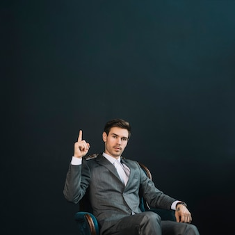 Confident smart young businessman sitting on armchair pointing finger upward against black background