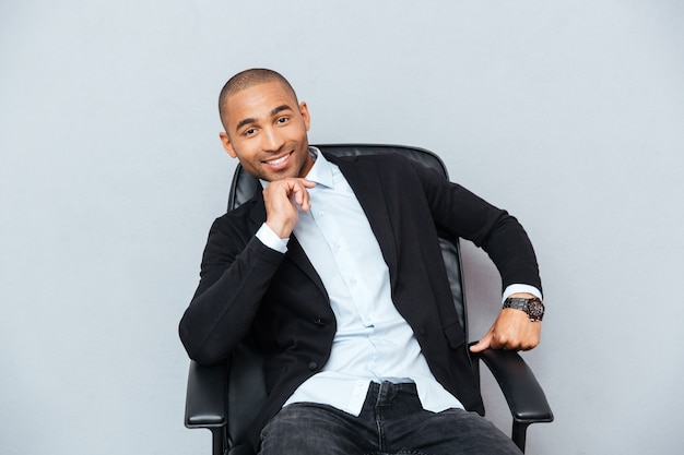 Confident smiling african american young man sitting in office chair