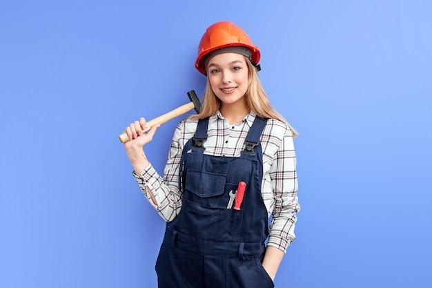 깨진 물건을 복구 할 준비가 손에 망치를 들고 자신감 웃는 건축가 여자