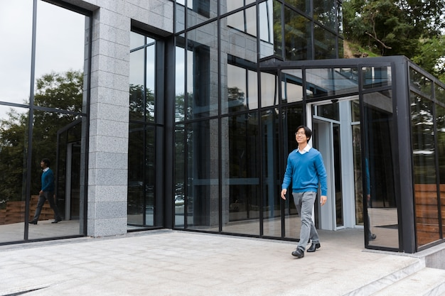 Confident smiling asian businessman leaving glass building