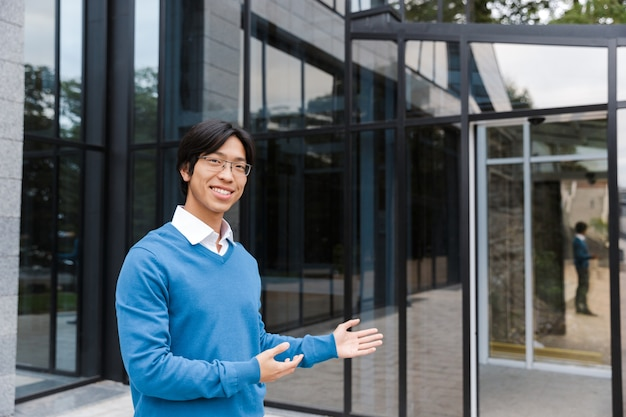 Confident smiling asian businessman standing at the glass building, welcome