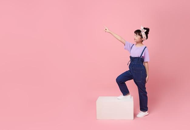 분홍색 외진 배경 옆에 있는 빈 공간에 손가락을 가리키는 자신감 있는 웃는 아시아 소녀