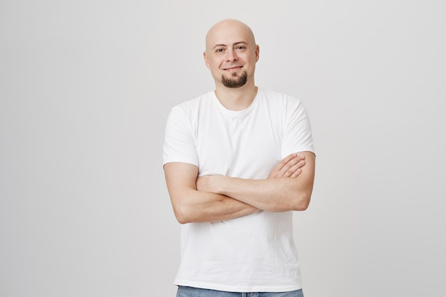 Confident smiling bald bearded man cross arms over chest
