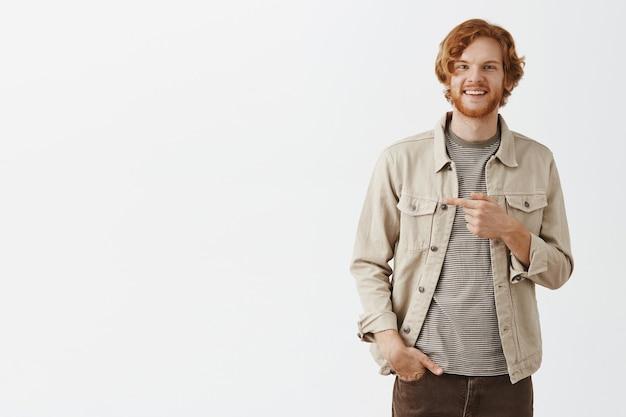白い壁に向かってポーズをとって自信を持って笑顔のひげを生やした赤毛の男