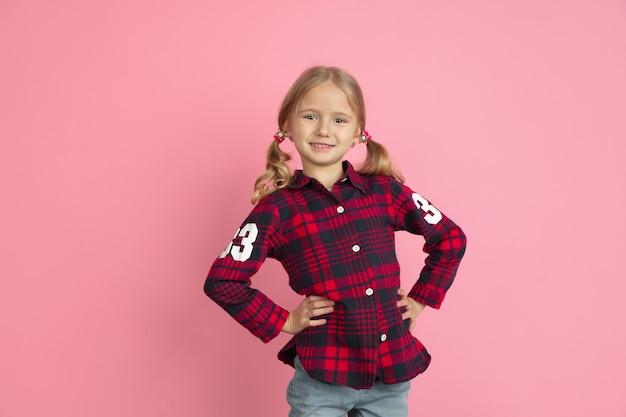 Sorridere sicuro. ritratto della bambina caucasica sulla parete rosa dello studio.