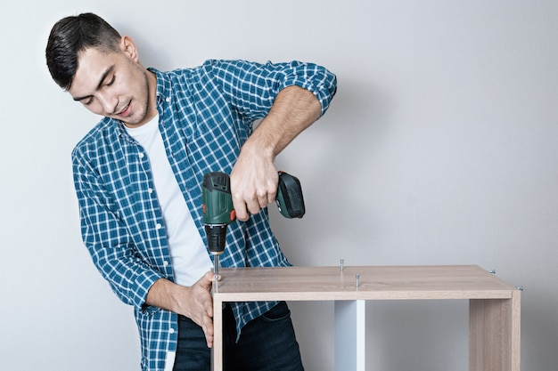 Confident smiling european man collects furniture with an electric screwdriver
