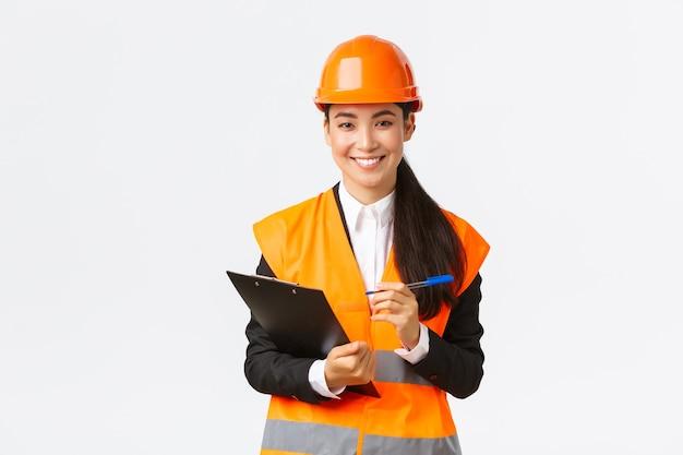 自信を持って笑顔の女性アジアの建設エンジニア、安全ヘルメットの産業女性が検査のために建物のエリアを訪問し、クリップボードにメモを書き、満足しているように見える、白い背景