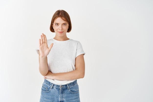 自信を持って笑顔の女の子はノーと言い、手のひらのジェスチャーを停止し、行動を禁止し、白い壁に立っています