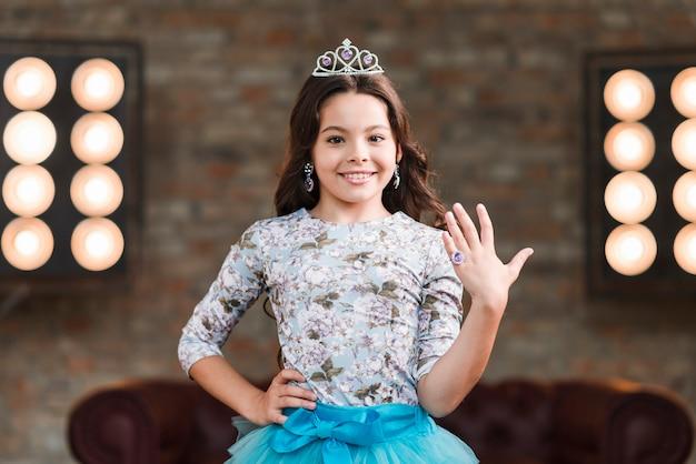Confident smiling girl showing finger ring against stage light