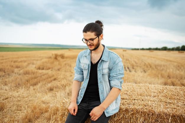 Confident smiling guy in denim jacket sitting on haystacks in farm field.