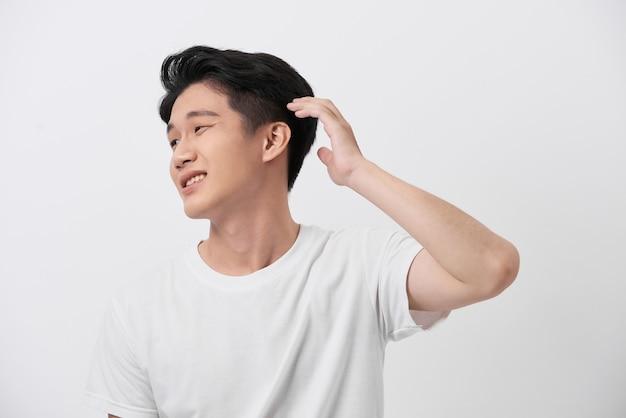 白いtシャツで自信を持って笑顔のハンサムな若い男。純粋な背景の上に立って、彼の完璧な髪型を修正します