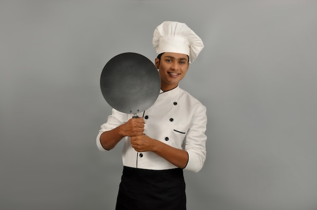 Confident smiling indian chef smiling behind the frying pan on grey background