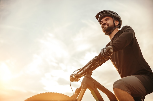 Confident smiling male bicyclist riding modern mountain bike