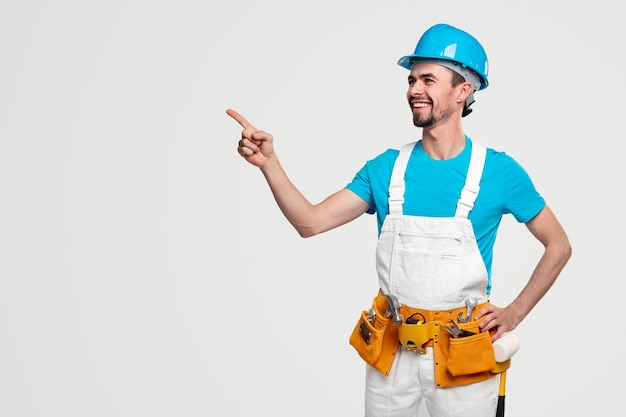 Confident smiling male worker in overall and hardhat with toolkit pointing at empty space