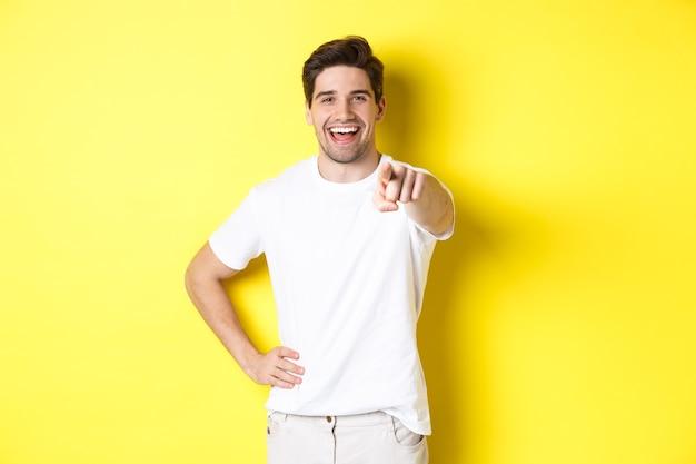Fiducioso uomo sorridente che punta alla telecamera, in piedi in abiti bianchi su sfondo giallo.