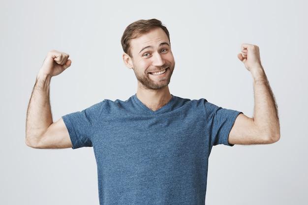 自信を持って笑顔の男がジムでトレーニング、強い上腕二頭筋を曲げ、筋肉を表示