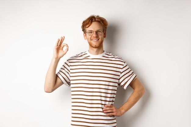 Уверенно улыбающийся человек с рыжими волосами, заверяя вас, показывая знак ок, гарантируя качество, рекомендуя что-то хорошее, стоя на белом фоне.