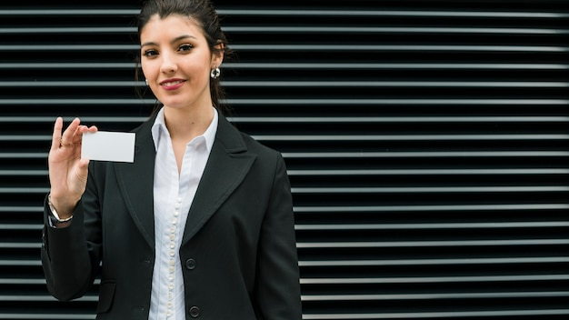 Confident smiling portrait of a smiling young businesswoman showing white business card