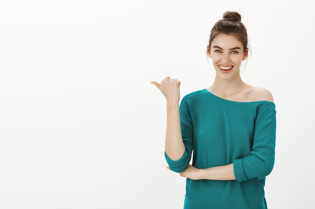 Confident smiling pretty woman showing your logo, pointing at banner left empty space