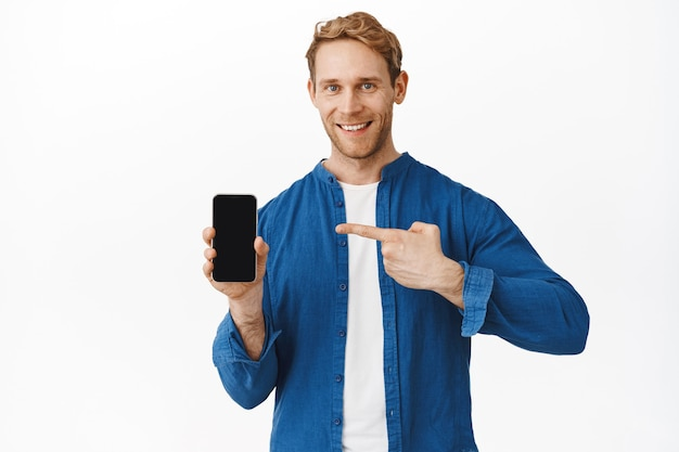 Confident smiling redhead man pointing at phone screen and looking at front, recommending good application on smartphone, display shopping deal, white wall