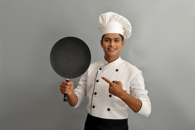 Confident smiling successful indian chef holding a frying pan and pointing profession