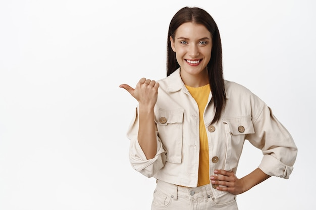 Confident smiling woman pointing left at sale discount banner, showing logo on white empty space recommending click on link, follow that way