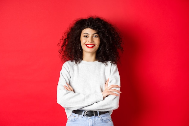 自信を持って笑顔の女性は、胸にメイクと巻き毛のヘアスタイルのクロスアームを持ち、プロのように見えます...